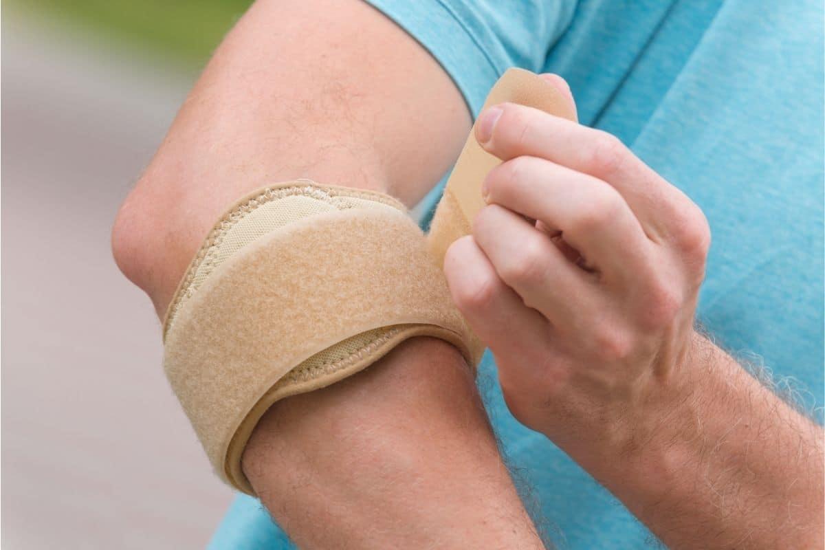 Man fixing elbow brace to reduce symptoms
